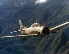A Ravens North American T-28 Trojan flies over the mountainous terrain of Laos, loaded with underwing rocket pods