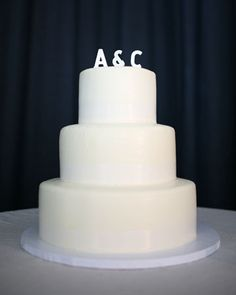 Love the simplicity of this all-white three-tier Italian buttercream cake topped with the newlyweds' initials
