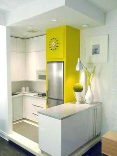 small kitchen with white cabinets and lime wall