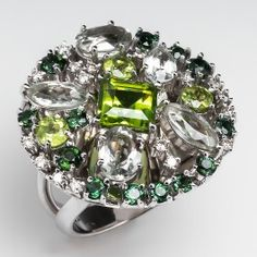 Denoir Green Gemstone & Diamond Cocktail Ring 18K White Gold. This large gemstone cocktail ring has a circular head set with prasiolite, peridot, and tourmaline all in different shades of green, and accented with diamonds. The circle sits atop a split shoulder shank and the ring is crafted of solid 18k white gold.