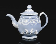 A RARE WEDGWOOD BLUE JASPERWARE TEAPOT AND COVER, CIRCA 1785, of ovoid form with a fluted spout and a pale-blue solid jasper body, sprigged in white relief with groups of putto and scenes from 'Domestic Employment' after designs by Lady Templetown, below an ornate flower and scroll border issuing from a fluted handle, impressed Wedgwood mark. 13.3cm., 5 1/4 in. high