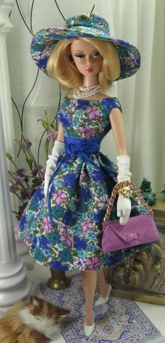 "A ""Mad Men"" style full skirted dress cut from a beautiful floral print challis, fully lined, with cap sleeve, scoop front neckline, plunging back neckline and button over snap back closure. A ruched waist treament is deep orchid china silk with dark blue silk ribbon bow accent. The matching sunhat is fully lined. The handbag is mulberry ultrasuede with gold-tone ""Chanel"" style chain strap and top stitching details and bow over snap to close the flap. $95.00us SHOES,, GLOVES, JEWELS, ..."