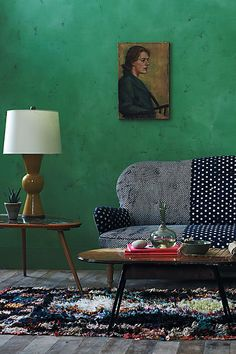 Love the couch colors, rug, lamp, bold wall color. The couch doesn't look comfortable though. Would prefer an ottoman to put feet up.