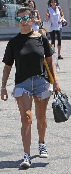 Kourtney Kardashian: Sunglasses – Quay  Shirt – Storets  Purse – Hermes  Bracelet – Cartier  Shorts – R31  Shoes – Converse