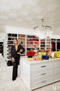 Khloé Kardashian in her vast master closet; the chandelier is by RH, and the ceiling is lined in a Schumacher wallpaper | archdigest.com