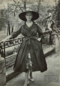 1957 Сhristian Dior a choisi une mousseline vert bronze, tout imprimée de muguets, pour cette kobe légère. Elle se complète d'un manteau en faille verte, à encolure très dégagée, noué d'une ceinture.