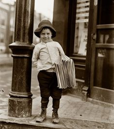 "Little Fattie: May 9, 1910. St. Louis, Mo. ""Newsboy. Little Fattie. Less than 40 inches high, 6 years old. Been at it one year."" Photo by Lewis Wickes Hine. ""His shoes, and the sidewalk and the base of the streetlamp show clearly how physically dirty life was back then. Add to this probably once a week baths and it really was incredible. """