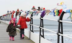 """A MYSTERY """"yarnbomber"""" has attached a 150ft Olympics-themed scarf to a Victorian pier in England in honor of the upcoming Olympics"""