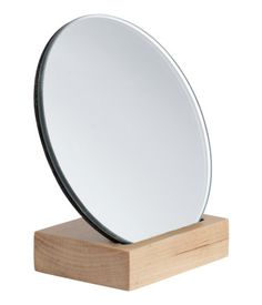 Beige. Small, round mirror with a wooden back and base. Diameter of mirror approx. 4 3/4 in., height 4 3/4 in.