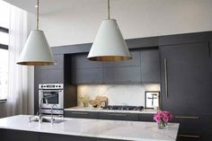 Athena Calderone.  Adding decorative hardware is a simple and inexpensive way to transform your kitchen and make it swoon-worthy!  Brass is also called out in the oversized Aero light fixtures that hang above the honed calacutta marble island.