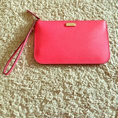 """NWT Kate spade leather wristlet Never worn. Tags still in bag (not attached). Geranium color on outside. White and black pattern on inside with slots for credit cards. Wristlet strap, top zip closure. 7w x 4.25""""h kate spade Bags Clutches & Wristlets"""