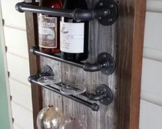 Reclaimed wood turned into a stylish wine rack display, with places to display three bottles of wine and wine glass, including a spot to hand a towel and wine opener. Great gift for the wine aficionado. Completely customizable size, shape, different pipe layouts, colors, etc... Message me with questions or custom order pricing quotes.  Thanks for visiting, check out my shop: UrbanStylesShop