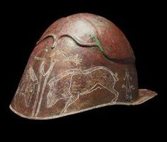Pseudio-Corinthian helmet, 5th-4th century B.C. With broad flat rear flange, the moulded eyebrows extending into ridge around the crown, attachment holes on the crown and at either side on the lower edge, the decoration comprising delineation of the eye-holes and nose-guard with confronting boars below, highlighted later in white,17.8 cm high, no apertures, the eyes, nasal and cheek-guards are indicated only by incision, probably a votive offering. Private collection, from Christie's auction