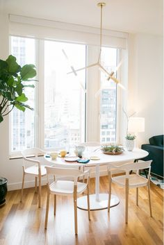 Dining area with oval white table and white and wooden chairs, and a brass modern light fixture.