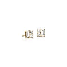 These unique earrings are comprised of a single round, princess, and baguette cut diamond set in 14k yellow gold.