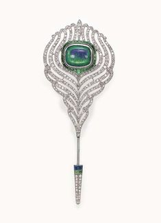 AN ART DECO OPAL AND DIAMOND JABOT PIN  Designed as a openwork single-cut diamond feather, centering upon a bezel-set rectangular cabochon opal within a calibré-cut emerald surround, joined by a single-cut diamond, calibré-cut emerald and sapphire terminal, mounted in platinum and 18k white gold, circa 1925