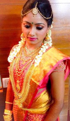 Our bride Mounya looks beautiful in a traditional attire for her muhurtam. Makeup and hairstyle by Swank Studio. Pink lips. Jhumkis. Maang tikka. Nose stud. Bridal jewelry. Bridal hair. Silk sari. Bridal Saree Blouse Design. Indian Bridal Makeup. Indian Bride. Gold Jewellery. Statement Blouse. Tamil bride. Telugu bride. Kannada bride. Hindu bride. Malayalee bride. Find us at https://www.facebook.com/SwankStudioBangalore