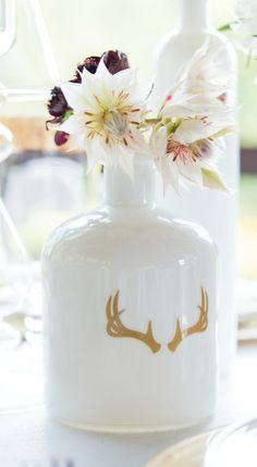 white glass bottle w gold antlers
