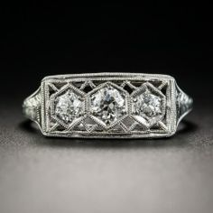 A trio of bright European-cut diamonds sparkle from within floating hexagonal settings in this pristine and precious original Jazz Age jewel, die-struck and hand-finished in platinum during the pinnacle of the Art Deco period - circa 1920s-30s. The edges and lattice work are accentuated with dinstinctive milgraining, and the side gallery and shoulders are artfully hand-engraved with neoclassical design motifs. A beauty. Currently ring size 6.