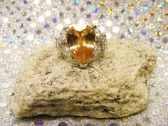 Silver ring with citrine gem. The citrine crystal is known for being a joyful stone with bright energy which lights up many aspects of lives of those who work with it. It has energies of good fortune and good luck, though these may appear in unexpected ways. Beautifully detailed with CZ's on both sides. Size 7 Only one I have. Gorgeous, unique ring that's never been worn.