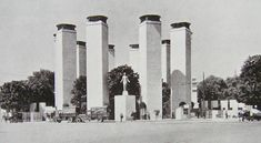 """Paris Exposition 1925. Porte de la Concorde; architect, Patout: The striking pylons by M. Patout and the bronze figure of """"Welcome"""" at the Porte de la Concorde were suggestive of some strange worship. They marked an entrance but did not form one. It was difficult, however, to imagine any other satisfactory solution since none of the trees were to be interfered with"""