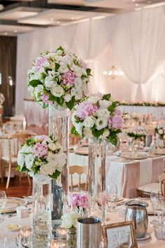 Tall floral centrepieces in clear vases. Simple and elegant