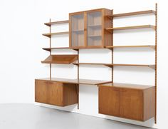 Sold Wall mount system with shelves, a desk and cabinets in teak. Design by Kai Kristiansen for FM Feldballe. Made in Denmark. Dimensions Width 257 cm