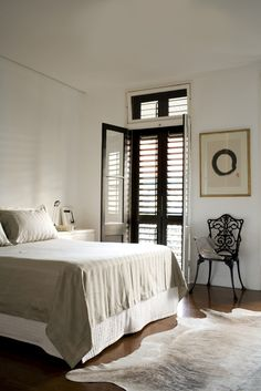 Floor to ceiling shutters are an effective way to keep the sun out in a warm climate. Bedroom design from a flat in Sydney designed by Hannah Tribe of Tribe Studio Architects. | #Bedroom #InteriorDesign |