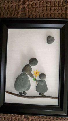 Un tableau avec des galets représentant grand-mère recevant une fleur en cadeau de son petit-enfant.18 idées de cadeaux DIY à offrir à grand-mère