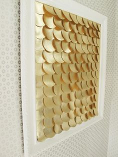 DIY art! Can't decide what these circles are made from... white frame and gold scales / perhaps made from spray painted card stock.