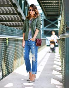 An army jacket is worn with ripped jeans, a grey T and pumps.