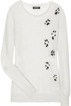 DKNY Cashmere paw-print sweater.   Add a playful element to fall dressing with DKNY's cream cashmere paw-print sweater. Team this chic knit with off-duty denim for a touch of animal magic. Cream cashmere sweater with black paw-print motif through front at one side. DKNY sweater has long sleeves with wide ribbed cuffs, a round neck, is fine knit and simply pulls on. 100% cashmere.