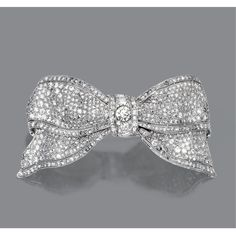 DIAMOND BOW BROOCH, CIRCA 1915. The bow-knot of arched form, set throughout with numerous old European-cut and single-cut diamonds weighing approximately 7.00 carats, mounted in platinum.