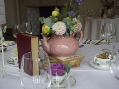 Flower filled tea pots and stacks of books for a vintage style table centre