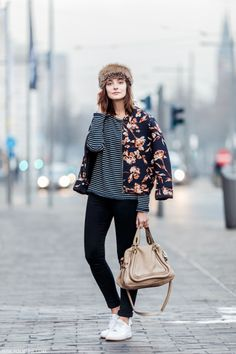A navy floral bomber jacket and black slim jeans are a great outfit formula to have in your arsenal. Round off this look with white low top sneakers.   Shop this look on Lookastic: https://lookastic.com/women/looks/bomber-jacket-long-sleeve-t-shirt-skinny-jeans-low-top-sneakers-satchel-bag-fur-hat/10268   — Brown Fur Hat  — Black and White Horizontal Striped Long Sleeve T-shirt  — Black Skinny Jeans  — Tan Leather Satchel Bag  — White Low Top Sneakers  — Navy Floral Bomber Jacket