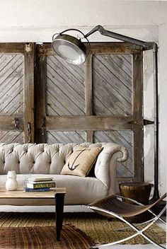 I love those old doors and the industrial light, mixed with the contempory chair and layered rugs