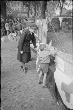 War Fair: Holidays at Home at a fete in Russell Square, London, 1943. A member of the Red Cross supervises as a young boy attempts to drive a nail into Hitler's coffin at the Russell Square fete. According to the original caption, the aim was to get the nail in within three swipes, although young children were given a head start! #wartime #WW2 #history