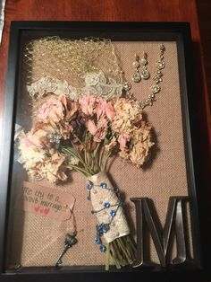 Wedding shadow box. What else to do with your wedding jewelry, bouquet, and other accessories? This box has my bouquet, birdcage veil, earrings, bracelet, initial of our married name and a word of advice from my bridal shower.