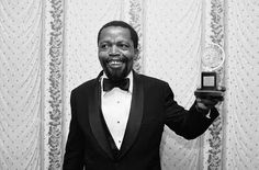 Zakes Mokae was born in Johannesburg, South Africa, moved to the UK in 1961, and to the US in 1969. He started acting at the same time as playwright Athol Fugard was emerging. The two worked together on Fugard's first success, The Blood Knot, about brothers with the same mother but different fathers; Zach (played by Mokae) is dark skinned and Morris (played by Fugard) is fair skinned. They also worked together on Master Harold and the Boys, for which Mokae won a 1982 Tony Award.