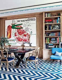 The dining room stars a painting by Andy Warhol and Jean-Michel Basquiat; model Ferraris are displayed on the custom-made ebony-and-steel table, and the zigzag-pattern floor—as in the adjoining living room—was hand-painted.