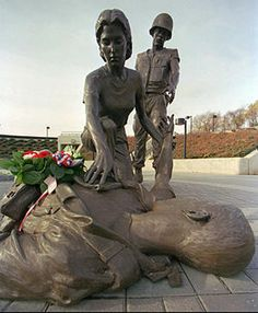 A small wreath of flowers rests on a sculpture of a military nurse helping a soldier as the soldier reaches out to another inside the New Jersey Vietnam Veterans Memorial in Holmdel, N.J., Nov. 10, 1997.