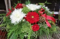 Christmas centerpiece with red gerberas, white spiders, red carnations with pine cones and ribbon
