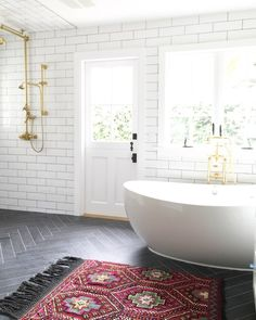 "The dark flooring and brass details in this bath called for a rug with an equally strong presence, says Owens. At the same time, ""the fringe edges and a detailed pattern soften the space."""