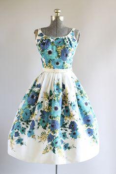 Deze jaren 1950 katoen piqué jurk van Pat Nichols van Miami functies een prachtige bloemen rand afdrukken in tinten van blauw, turquoise, groen en geel. Drievoudige spaghetti bandjes. Gesmoord taille en bevat de originele witte band. Volledige geplooide rok. Metalen rits omhoog