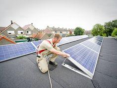 Een medewerker van SchoneStroomOost bezig met de plaatsing van zonnepanelen op het dak van het Denk en Zet clubhuis in Westerhaar. Foto: Lenneke Lingmont