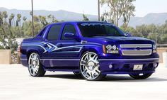 Blue custom 2011 Chevy Avalanche with chrome radiant wheels