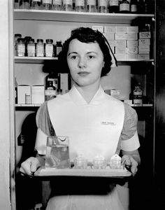 Early 1950s, an NEDH School of Nursing student prepares medicine for the evening rounds.