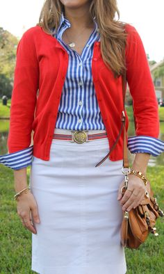 Blue oxford striped shirt with red cardigan and cream skirt or trousers