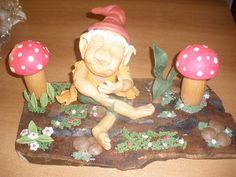 Duende en porcelana fría sobre una superficie de tronco de árbol