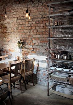 Brick wall, wooden table and chairs and metal shelf - industrial interior design